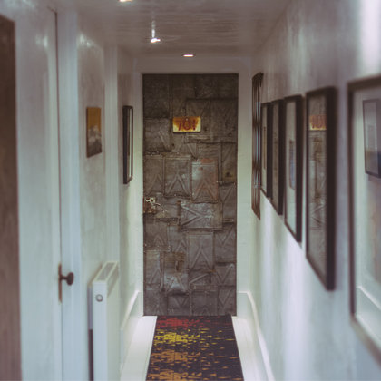 The amazing hallway leading to a custom built door made of salvaged metal. Makes you wonder what's behind that door, doesn't it?