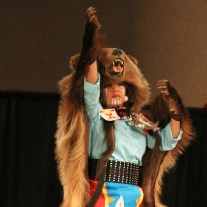 Laura Grizzlypaws performs a traditional dance with a grizzly bear skin.