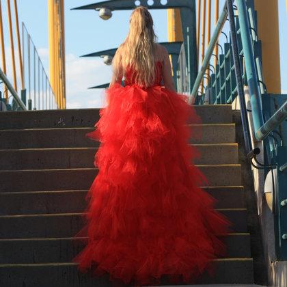 Model Dianna Flintoff wearings a red dress in honor of MMIWG.